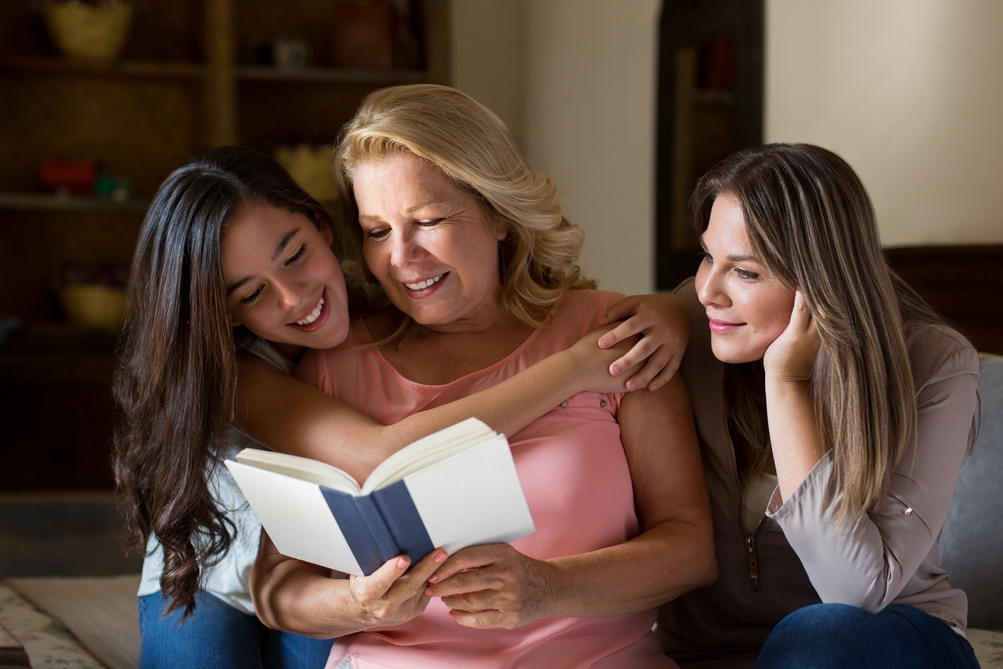 grandmother, mother, daughter reading together
